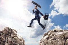 Geschäftsmann mit dem Regenschirm, der auf Berge springt lizenzfreie stockfotos