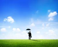 Geschäftsmann mit dem Regenschirm, der auf einem Feld steht Lizenzfreies Stockbild