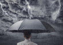 Geschäftsmann mit dem Regenschirm, der von näherndem Sturm schützt Stockfoto