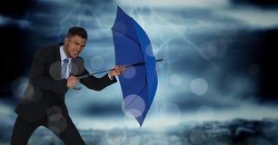 Geschäftsmann mit dem Regenschirm, der Wind gegen stürmischen Himmel und bokeh blockiert Stockbilder