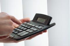 Geschäftsmann mit dem Taschenrechner, zählend auf Taschenrechner Lizenzfreie Stockfotos