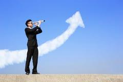 Geschäftsmann mit dem Teleskop, das vorwärts schaut Lizenzfreie Stockbilder