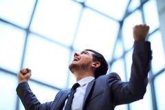 Geschäftsmann mit den Armen seinen Sieg oben feiernd Stockfoto