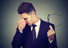 Geschäftsmann mit den Gläsern, die unter Augenermüdung leiden lizenzfreies stockbild