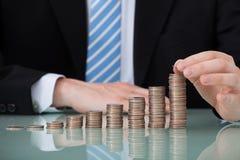 Geschäftsmann mit den Münzen gestapelt als Balkendiagramm Stockfoto