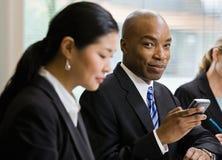 Geschäftsmann mit den Mitarbeitern, die Telefon anhalten Lizenzfreies Stockfoto