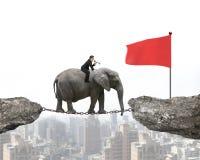 Geschäftsmann mit der Anwendung des Sprecherreitelefanten in Richtung zur roten Fahne Lizenzfreie Stockfotografie