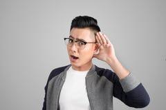 Geschäftsmann mit der Hand hinter Ohr hörend nah gegen Grau lizenzfreie stockfotos
