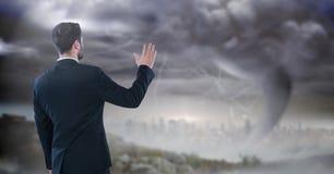 Geschäftsmann mit der Hand oben im Sturmstadtbild Stockfoto