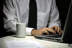 Geschäftsmann mit der Kaffeetasse, die an Laptop arbeitet Stockbild