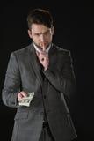 Geschäftsmann mit der Stillegeste, die Dollarbanknoten lokalisiert auf Schwarzem hält Lizenzfreies Stockfoto