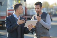 Geschäftsmann mit digitaler Tablette draußen sprechend mit Arbeitskraft lizenzfreie stockfotos