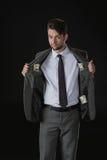 Geschäftsmann mit Dollarbanknoten in den Taschen lokalisiert auf Schwarzem Stockfoto