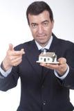 Geschäftsmann mit einem kleinen Haus in seiner Hand lizenzfreies stockfoto