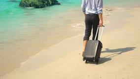 Geschäftsmann mit einem Koffer geht auf einen weißen sandigen Strand Konzept des Freiberuflich tätig seins, Ferien stock footage