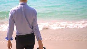 Geschäftsmann mit einem Koffer geht auf einen weißen sandigen Strand Konzept des Freiberuflich tätig seins, Ferien stock video