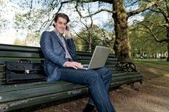 Geschäftsmann mit einem Laptop, der in einem Park sitzt stockbild