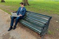 Geschäftsmann mit einem Laptop, der in einem Park sitzt stockfoto