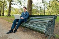 Geschäftsmann mit einem Laptop, der in einem Park sitzt stockfotografie