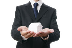 Geschäftsmann mit einem Papierhaus in den Händen Stockbilder