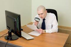 Geschäftsmann mit einem Vergrößerungsglas auf einem Arbeitsplatz Lizenzfreies Stockfoto