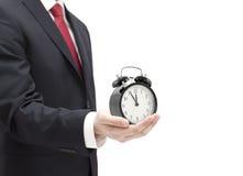 Geschäftsmann mit einer Alarmuhr in einer Hand Lizenzfreies Stockfoto