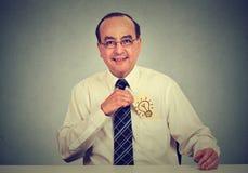 Geschäftsmann mit einer großartigen Idee, die eine Karte mit Glühlampe von seiner Hemdtasche zurücknimmt Stockfoto