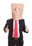Geschäftsmann mit einer Papiertüte mit Lächeln auf dem Kopf, der okayzeichen zeigt Stockfotografie