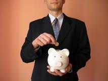 Geschäftsmann mit einer Piggy Querneigung Stockfoto