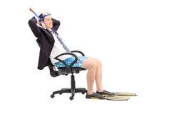Geschäftsmann mit einer Schnorchel, die in einem Bürostuhl sich entspannt lizenzfreie stockfotos