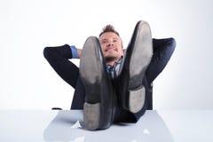 Geschäftsmann mit Füßen auf Schreibtisch Lizenzfreies Stockbild