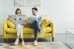 Geschäftsmann mit Fraulesezeitungen über Reise und Geschäft beim Sitzen auf Sofa im modernen Raum stockfotos