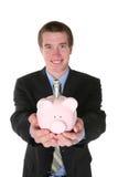Geschäftsmann mit Geld (Fokus auf Piggy Querneigung) Lizenzfreie Stockbilder