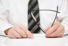 Geschäftsmann mit Gläsern in der Hand liest sorgfältig Vertrag Stockbild