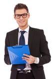 Geschäftsmann mit Gläsern schreibt auf Klemmbrett Lizenzfreies Stockfoto