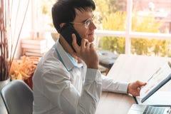 Geschäftsmann mit Gläsern um Handy ersuchend lizenzfreie stockfotos