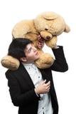 Geschäftsmann mit großem weichem Spielzeug auf Schultern Lizenzfreie Stockbilder