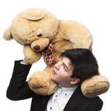 Geschäftsmann mit großem weichem Spielzeug auf Schultern Lizenzfreies Stockfoto