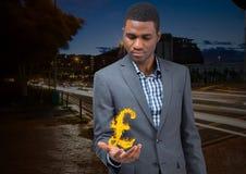 Geschäftsmann mit Handverbreitung von mit Pfund feuern Ikone vorbei in der Stadt nachts ab Lizenzfreie Stockbilder