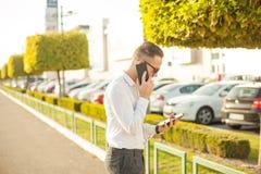 Geschäftsmann mit Handy und Tablette in den Händen Lizenzfreie Stockfotos