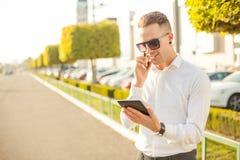Geschäftsmann mit Handy und Tablette in den Händen Stockfotografie