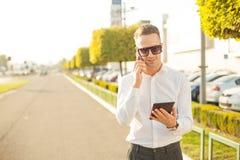 Geschäftsmann mit Handy und Tablette in den Händen Stockbild
