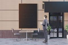 Geschäftsmann mit Kaffee nahe einem Café, Fahne Stockfoto