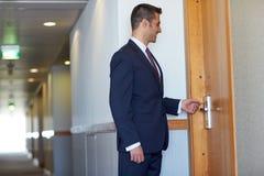 Geschäftsmann mit keycard an der Hotel- oder Bürotür Stockbild