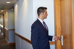 Geschäftsmann mit keycard an der Hotel- oder Bürotür Stockbilder