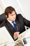 Geschäftsmann mit Kopfhörer Zeitplan überprüfend Lizenzfreie Stockbilder