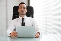 Geschäftsmann mit Kopfhörern und Laptop-Computer Stockfotografie