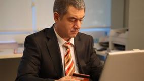 Geschäftsmann mit Kreditkarte, unter Verwendung des Laptops im Büro stock footage