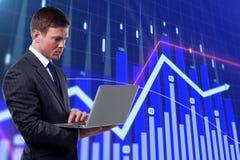 Geschäftsmann mit Laptop am Finanzdiagramm stockbild