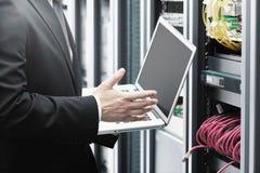 Geschäftsmann mit Laptop im Netzserverraum Lizenzfreie Stockfotografie